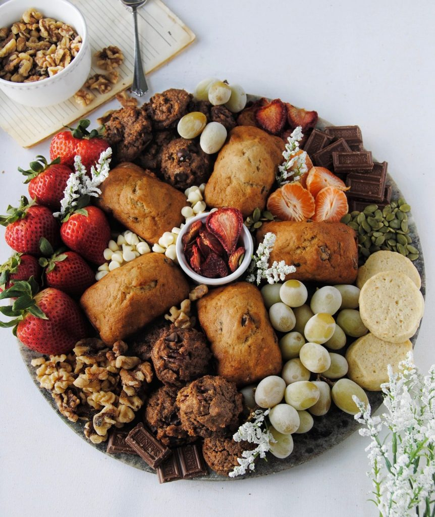 banana bread muffins brunch board with fruit and nuts